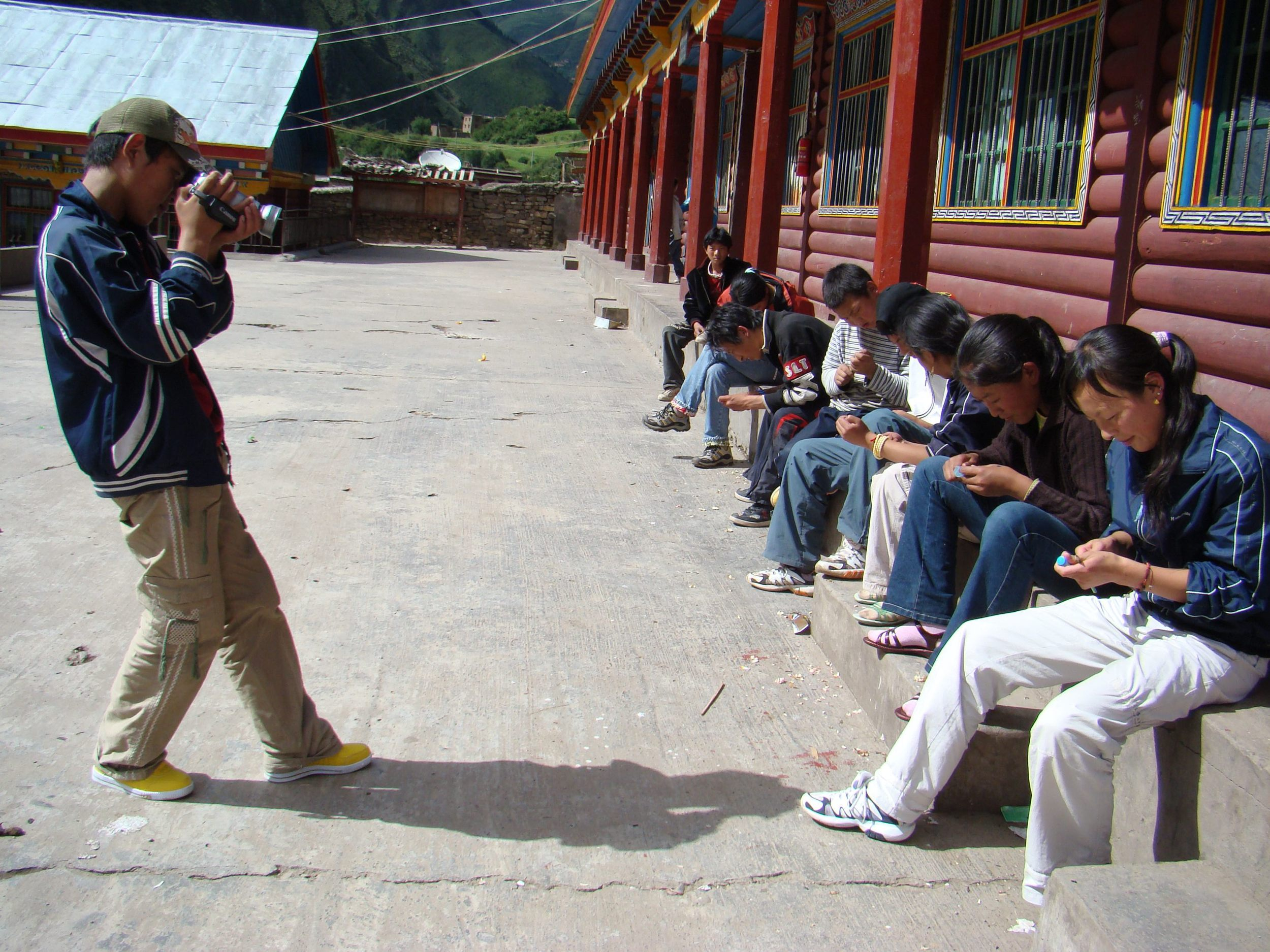 Dorjee Tashi films his classmates making wood carvings
