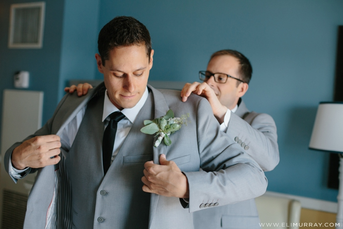 groom with groomsman getting into grey suit