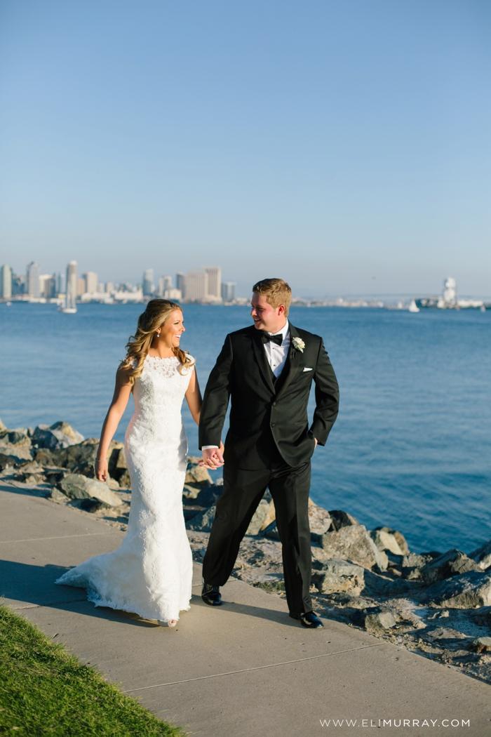 bride and groom walking near san diego skyline