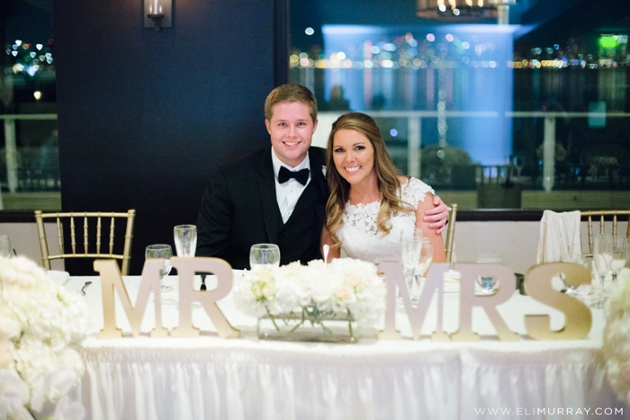 newlyweds at head reception table