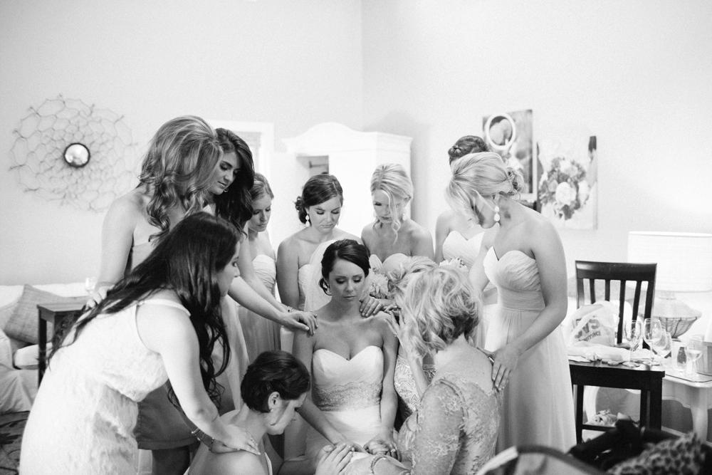 bridesmaids praying over bride