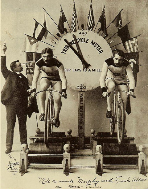 Famous speed bicyclist 'Mile-A-Minute' Murphy (left) and fellow cyclist Frank Albert race on a new stationary training machine. The Tribune Cycle Meter, decorated with international flags, measures the distance traveled. (Photo by Horner/Library of Congress/Corbis/VCG via Getty Images)