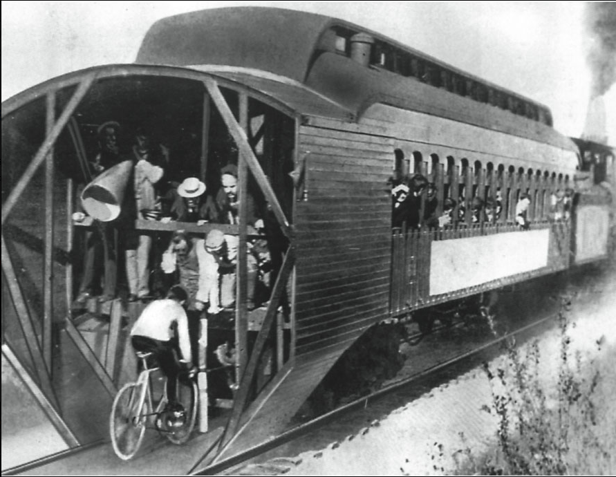Charles M. 'mile-a-minute' Murphy on his bicycle riding behind a Long Island Railroad train. Time: 57 4/5 seconds over the mile span. Photograph, June 30, 1899.