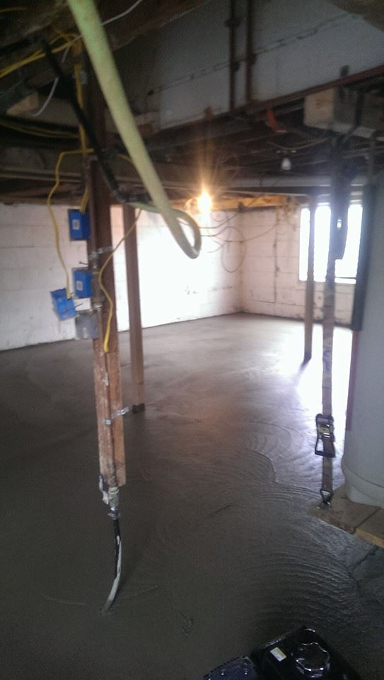 A concrete floor is being poured in the newly formed basement.