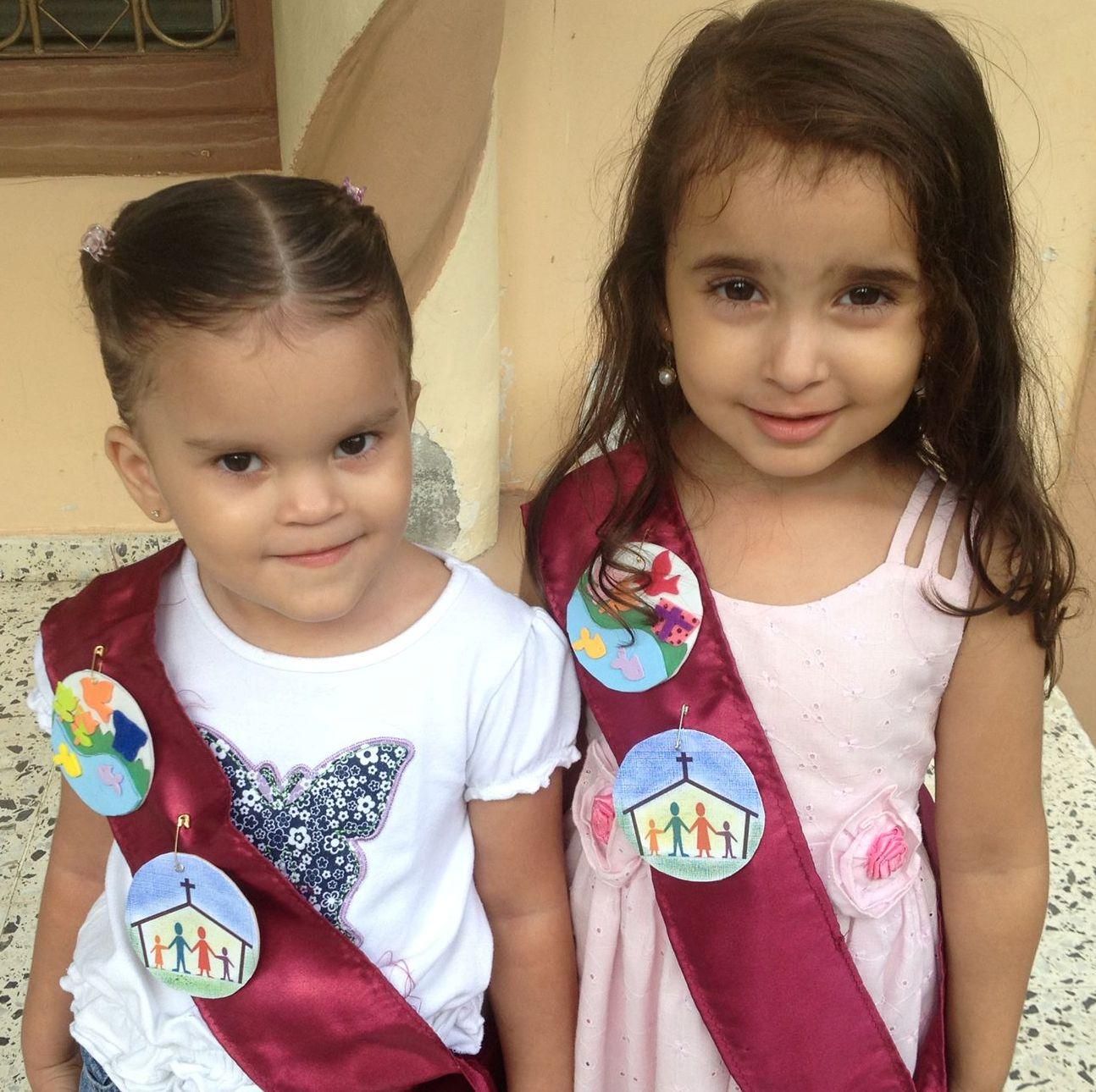 Dos niñas del programa Pececitos reciben sus reconocimientos en Honduras.