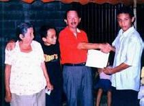 Ebenezer recibiendo el certificado de los manos de su hijo mayor por haber asistido y participado en esta primera etapa del programa Shalom. A la derecha está su hijo menor después la mamá.