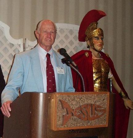 John Shackelford hablando durante un banquete de donares en Los Angeles en 2006 a lado de una estatua de un Legionario Romano mostrando la armadura de Dios.