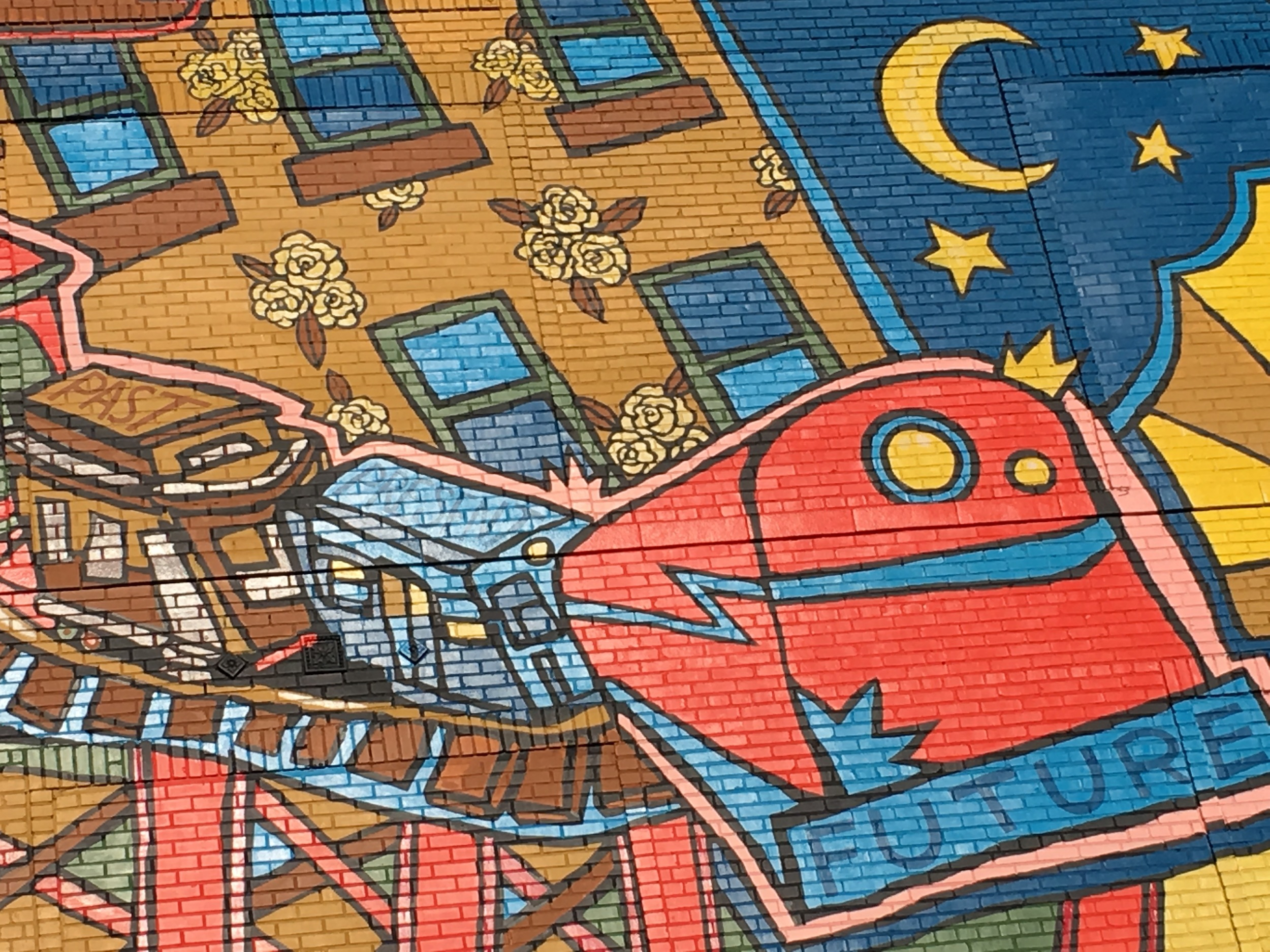 This close up reveals details of the image topic, and is contained within a frame chosen by the image creator. Out of all the features of this mural she chose to have us look at this train of change. We see the color of the past, the namelessness of the present, and the bright, streamlined presentation of the future.