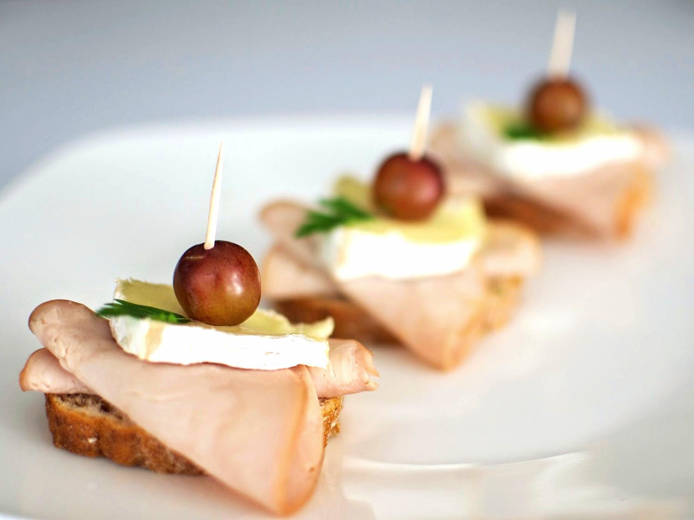 Tapas de Lomo Canadiense  Pan de centeno con lomo canadiense, queso brie y uva roja. (MÍNIMO 25 PIEZAS) PRECIO POR PIEZA  $ 17.00