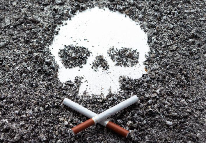 两根交叉的骨状香烟放在由烟草灰形成的头骨旁边.jpg