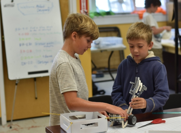 Two young engineers discussing robotic arm design