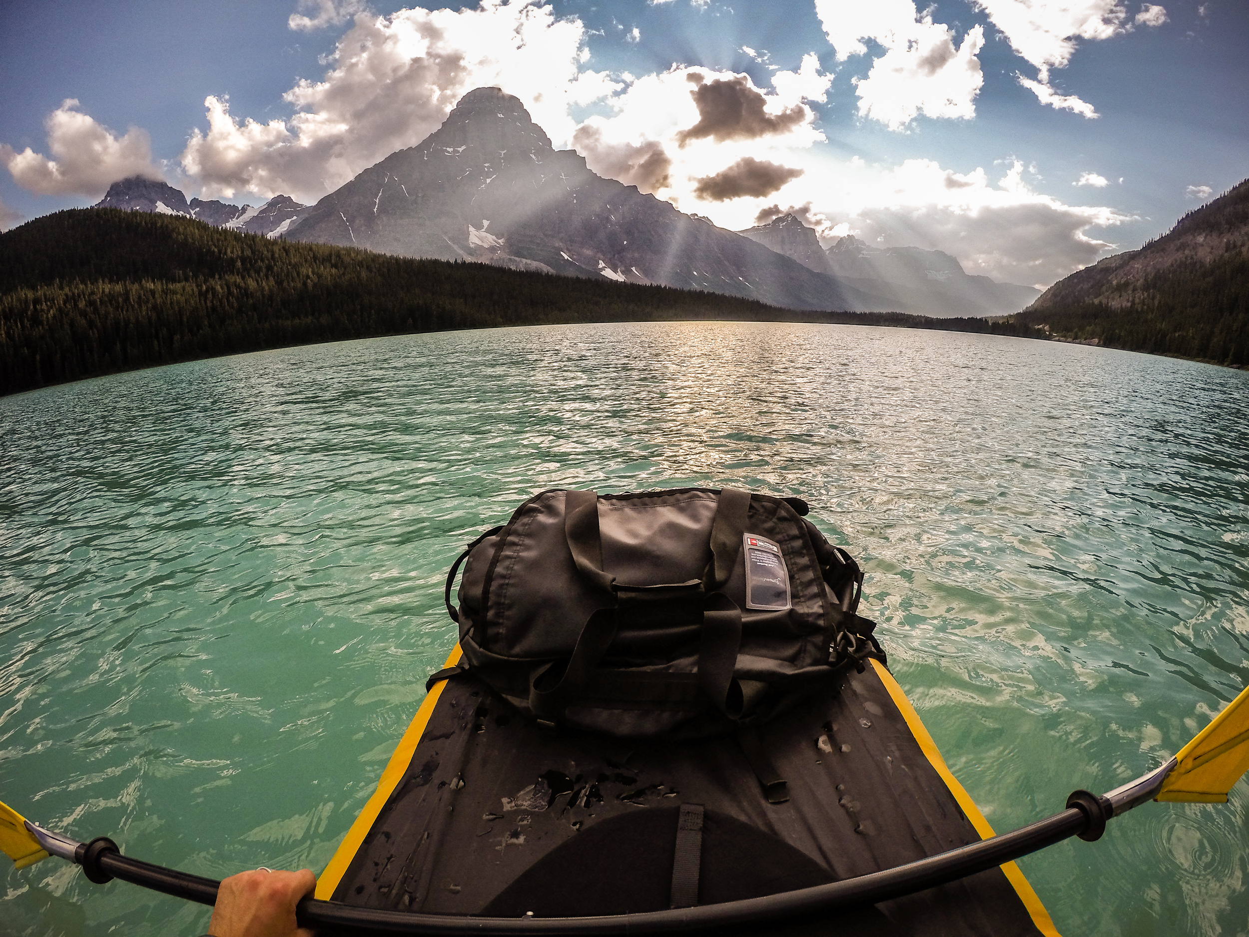 The sun breaks through the clouds onto @PhotoJBartlett packrafting on Waterfowl Lake.