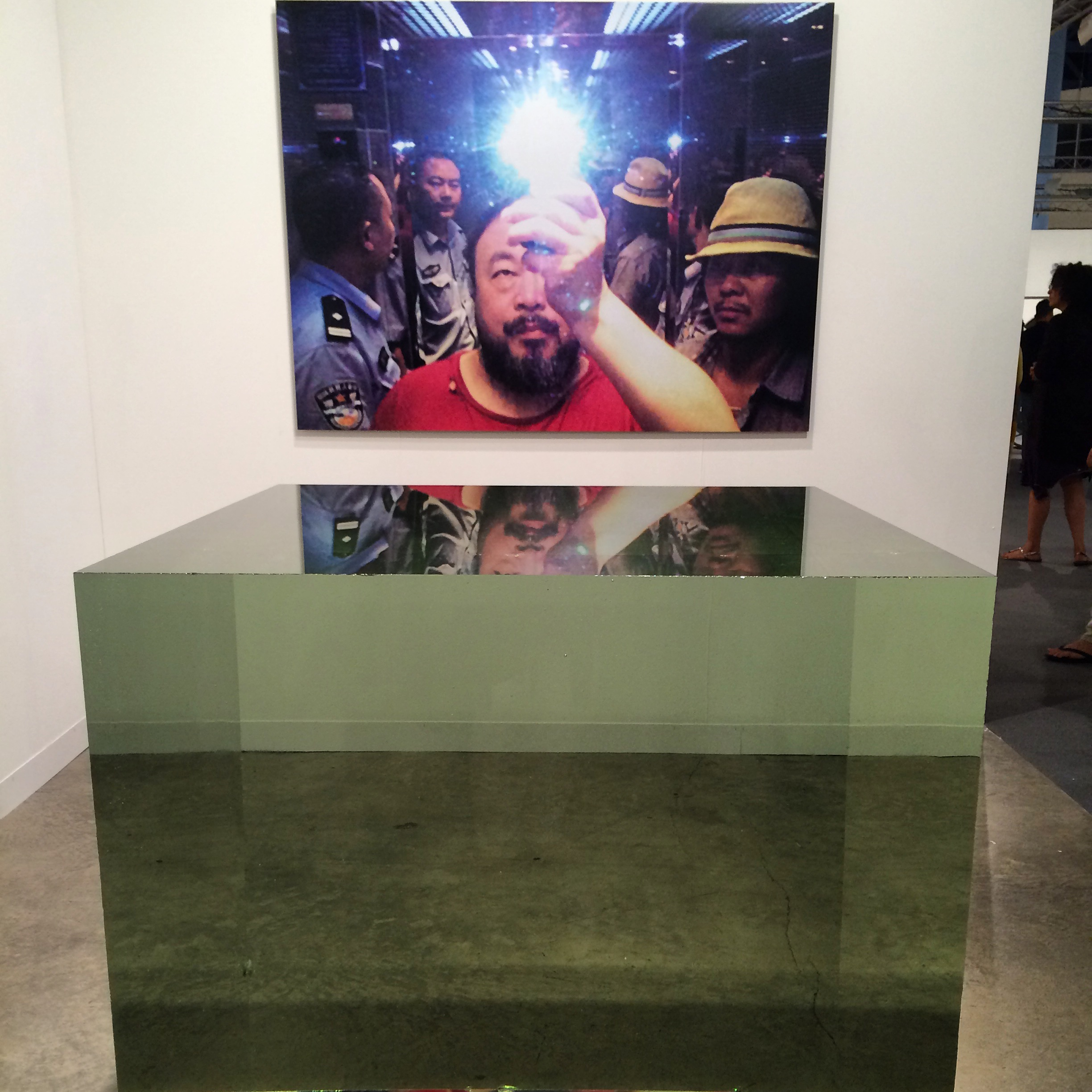 Ai Weiwei. Photograph and Crystal Cube, 2014. Crystal (leaded glass) cube 100 x 100 x 100 cm (1 cubic meter). Singular. Neugerriemschneider, Berlin.  Ai WeiWei's singular photo shows his arrest, taken in elevator with arresting policemen. His hand and the flash cover the bruises on his face from the arrest. Both works sold, separately, at very respectable prices. Ai WeiWei and other respected contemporary artists who consider glass as a medium of expression bridge the interesting gap of contemporary glass to contemporary fine art.
