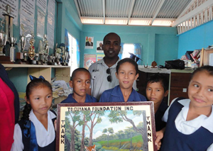 Students of Santa Rosa Primary donate a painting to Managing Director of The Guyana Foundation, Anthony Autar, after the school was given a $2M donation to upgrade its facilities.