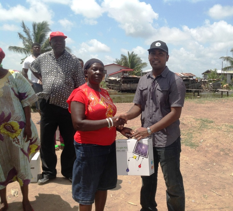 Managing Director of the Guyana Foundation, Mr. Anthony Autar, handing over a light kit to a resident of Breezy Point.