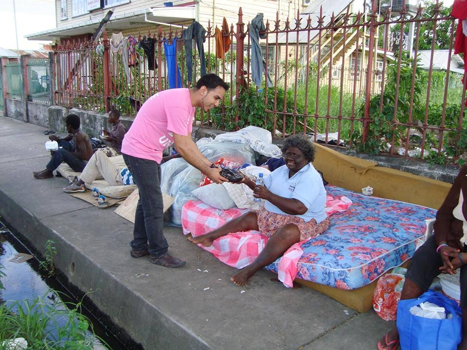 A Guyana Foundation volunteer handing over a hot meal to an individual living on the streets of Georgetown.