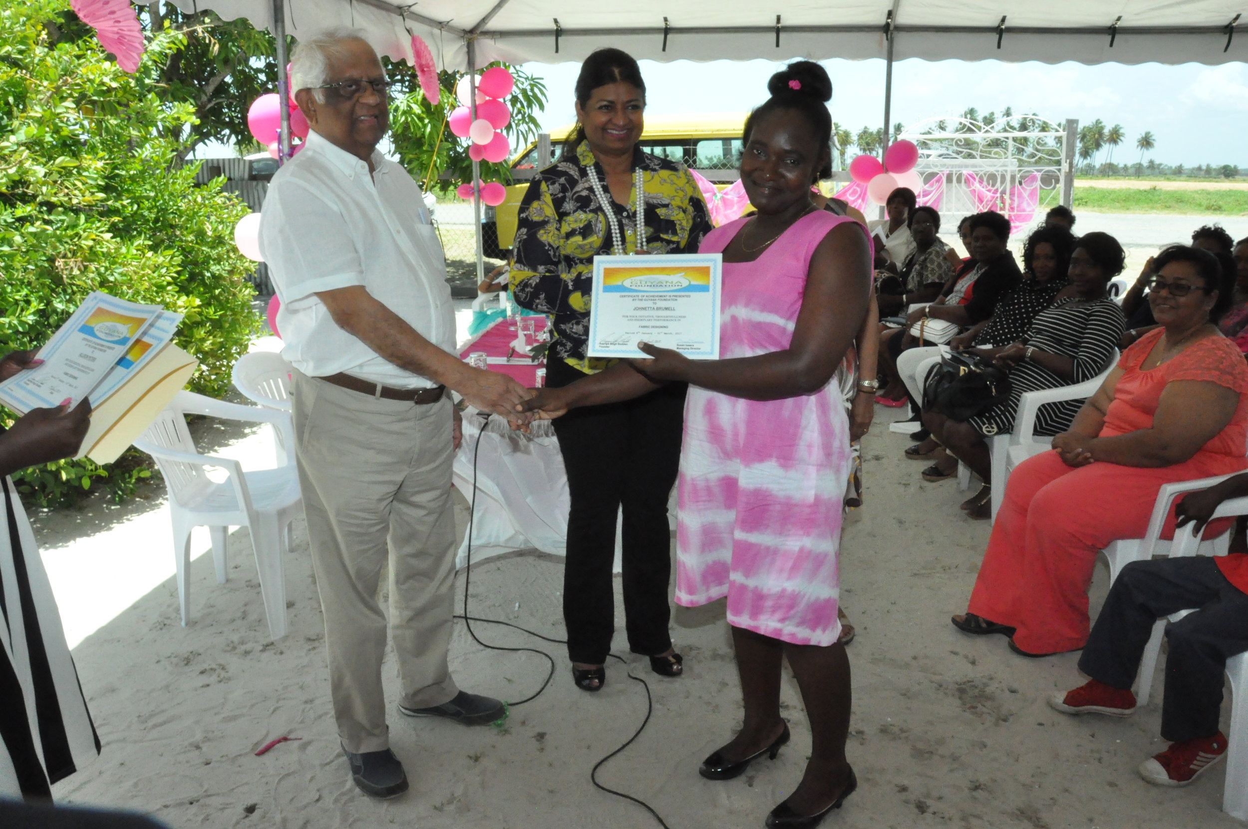 Dr. Ranjit Singh presenting a certificate to a student of the Fabric Design class.