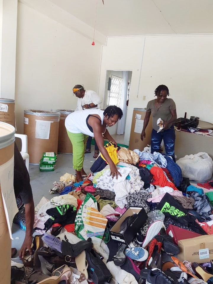 Volunteers helping to sort out clothing and shoes among other items.