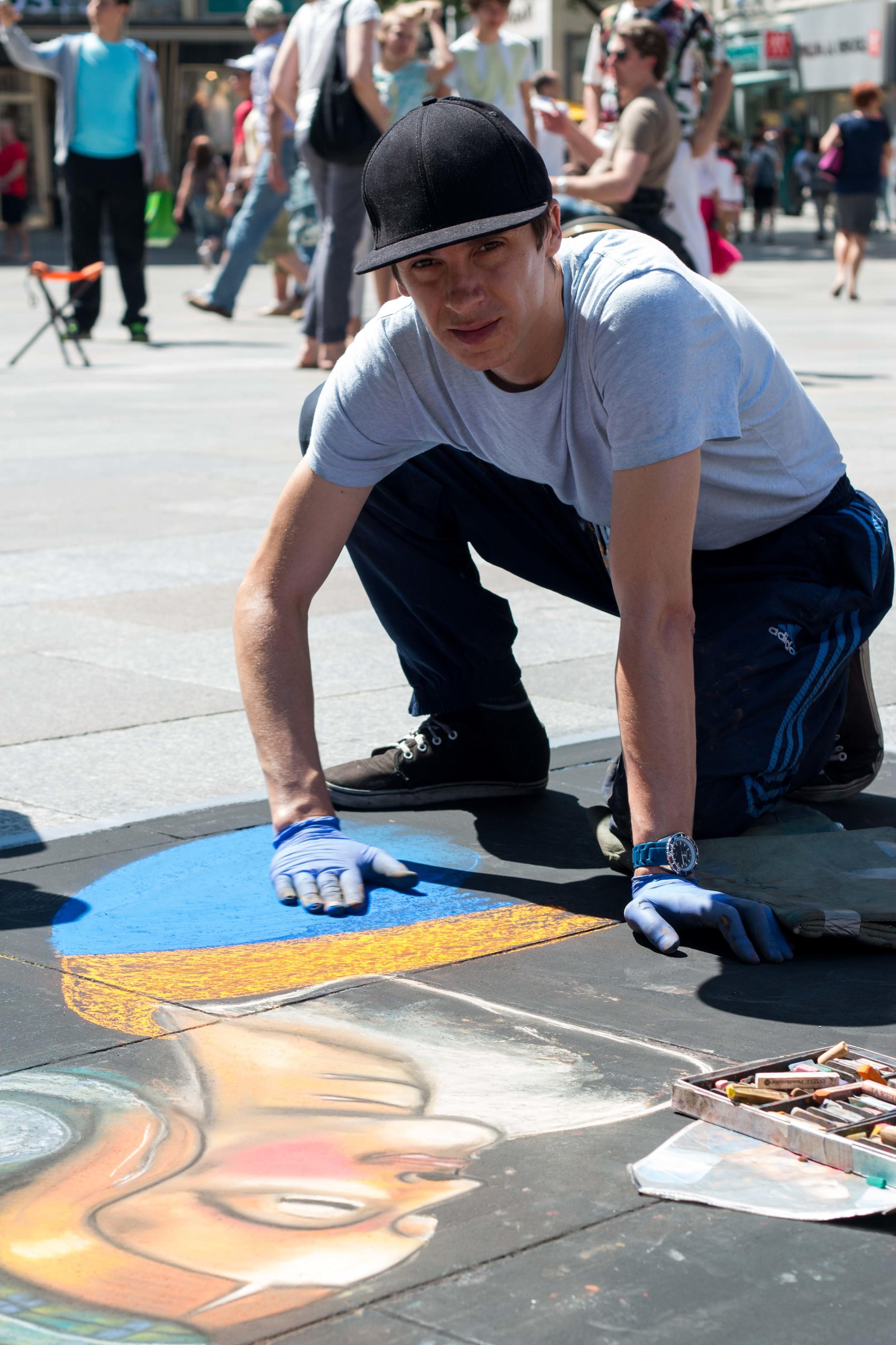 Street artist working on an amazing chalk painting