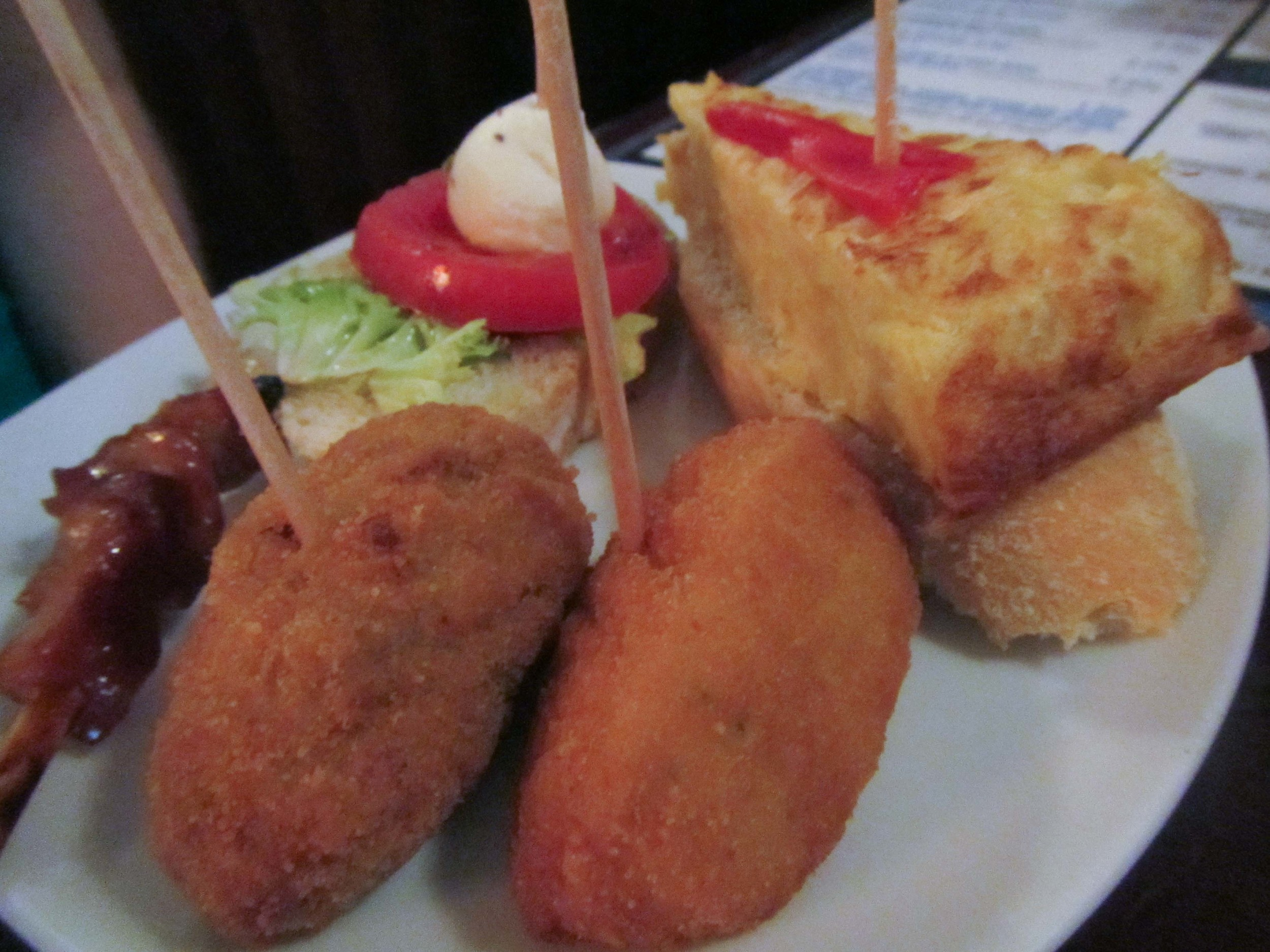 croquettes, capresse bread, potato quiche and some sort of meat on a stick