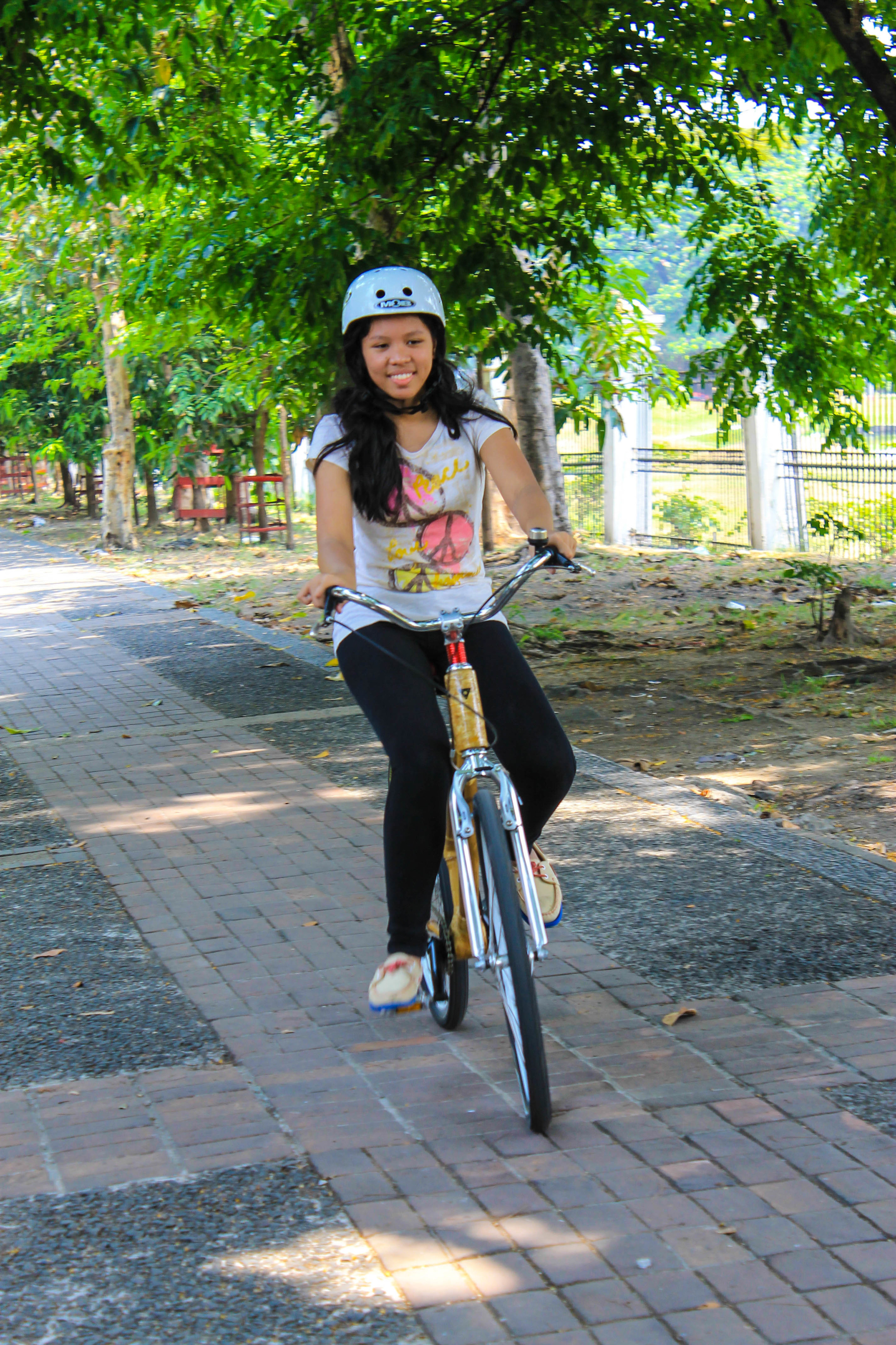 Bambike Intern Linet Dumag riding a company bicycles in the park.