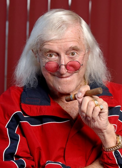 "(Via York Press) Secret plans have been revealed to exhume the corpse of Jimmy Savile from its concrete tomb.  The two-day operation was planned following complaints from families of loved ones buried in the graveyard. A contingency plan had been agreed with the Savile family to dig up the body but the charities the DJ left his fortune to said ""no"" because of the cost.  Now campaigners calling for Savile's corpse to be dug up hope money will still be left from his estate to meet the £20,000 bill for the exhumation.  When undertakers removed Savile's gaudy £4,000 triple gravestone from Scarborough cemetery in 2012 the work began after midnight and was completed by the early hours. But chipping the corpse out of the tomb raider-proof final resting place will involve closing the graveyard for a day, a night, and another day.  The six-foot wide triple plot had been filled to the brim with two-and- a-half tonnes of reinforced concrete with steel bars also inserted to bind the mix together.  The family was not comfortable with Savile's body remaining in the cemetery following calls by Scarborough Councillor Colin Haddington for it to be dug up and cremated.  The church had also made clear that ecclesiastical consent would not be a problem. But the trustees of the Jimmy Savile Charitable Trust were not happy. The charity drew the line at an exhumation, which bosses regarded as ""a luxury"" because the cash was supposed to be going to good causes, sources revealed.        Cllr Haddington said: ""The undertakers visited the family and the family agreed to the exhumation plan. But then the trust refused to release any money to pay for it.  ""That was disappointing because the Savile family felt it was a good idea to appease the relatives who had complained to me. I can understand the trust wanting to use the money to pay compensation to the victims. But it is just as important for the families who have loved ones buried there. As times move on some will forget – but others will not.  ""Jimmy Savile will be on their minds every time they lay flowers no matter how long it goes on. If someone comes up with the money the plans are still there and ready to go. It would be nice to think if there was anything left over from the estate it would be enough to do it."""