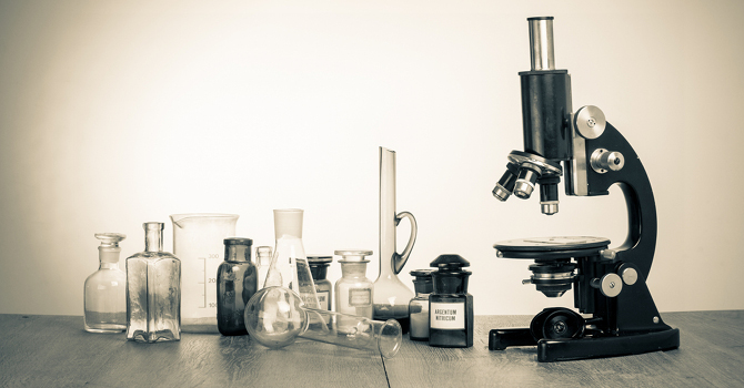 stock-photo-microscope-on-table-for-vintage-science-background-158353394.jpg