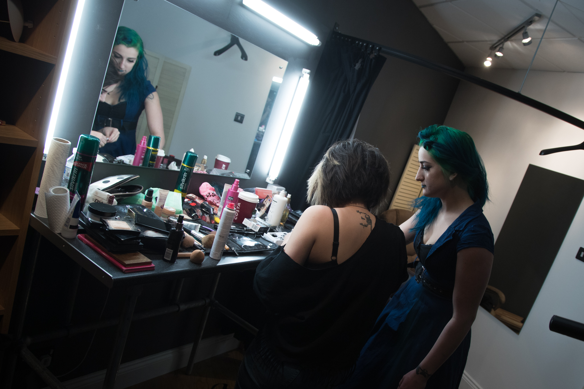 The Makeup area, a large mirror and table with power, and dimming surround light and a raised chair. The dressing room is visible on the right, it has a curtain along with mirror, bench, clothes rail and it's own light.