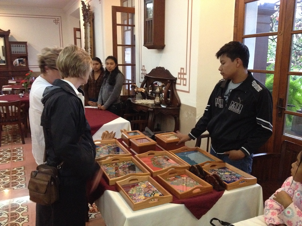 Roberto shows off the handcrafted wood-and-glass serving trays and keepsake boxes, with traditional huipil textiles.