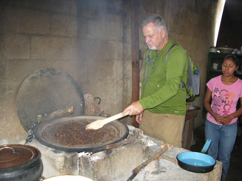 A tour participant roasts coffee beans, under the watchful eye of one of Filiberto's daughters.