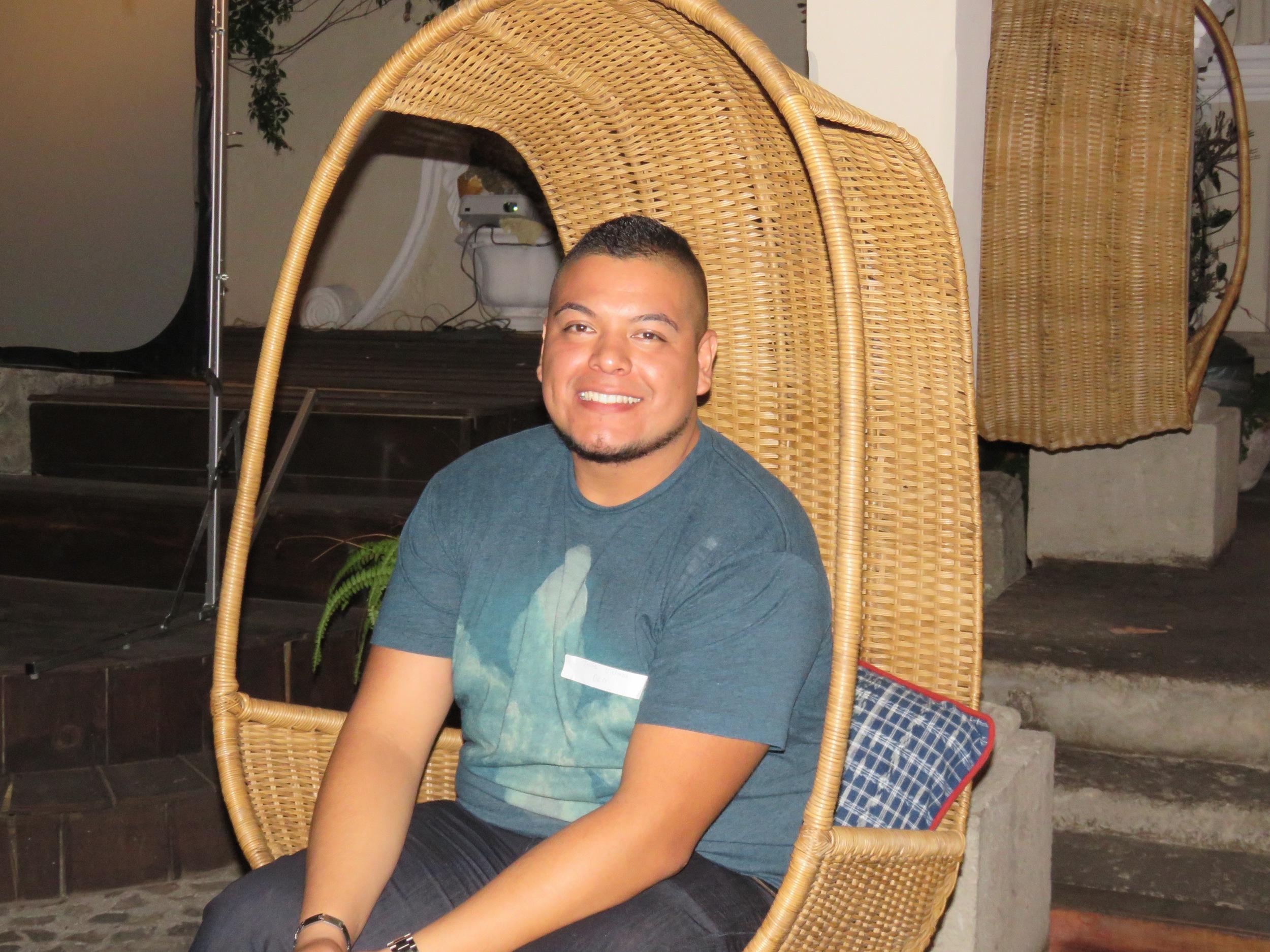 guy smiling in wicker chair