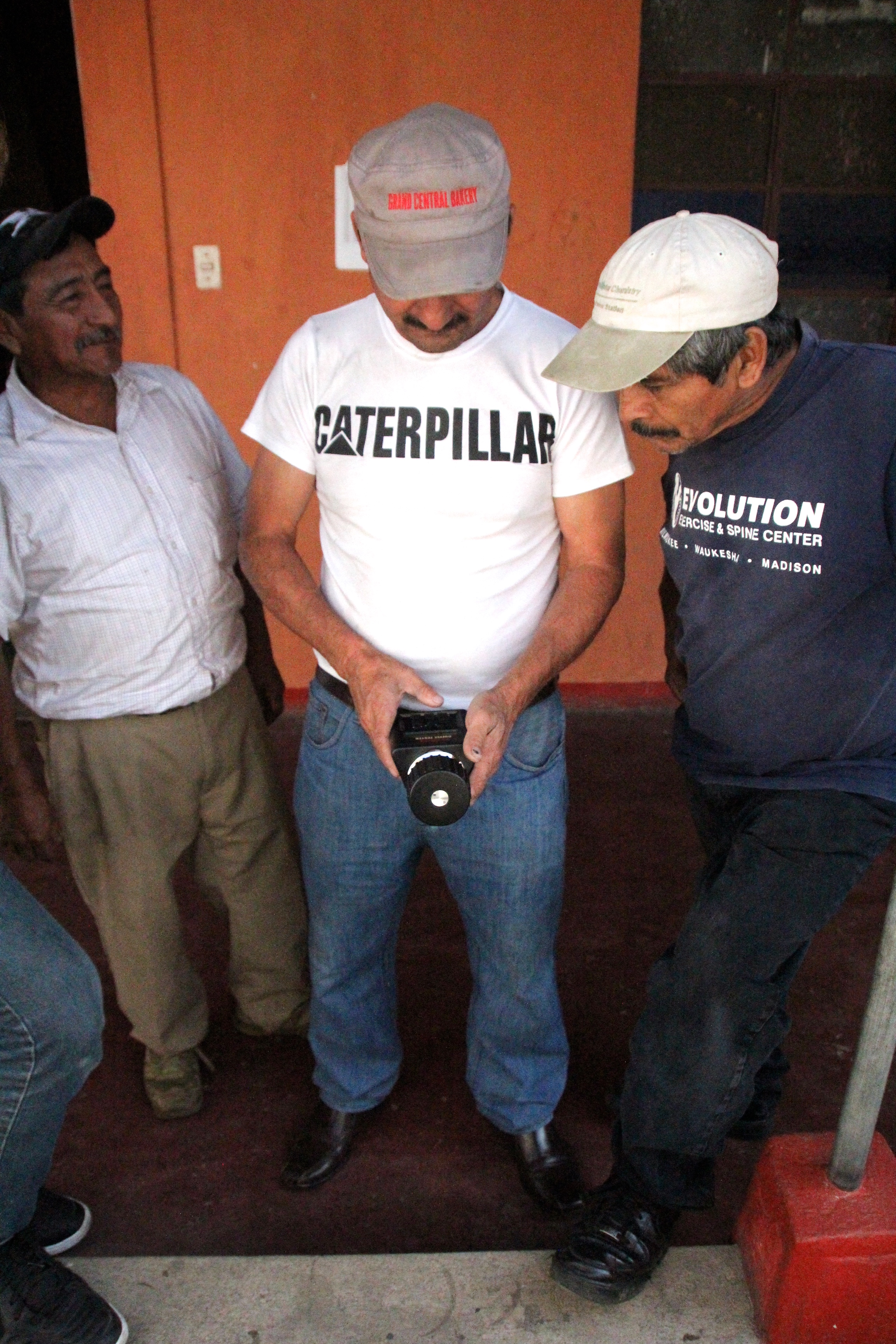Timoteo, Rigo, & Mincho using a humidity meter to test moisture levels in coffee.