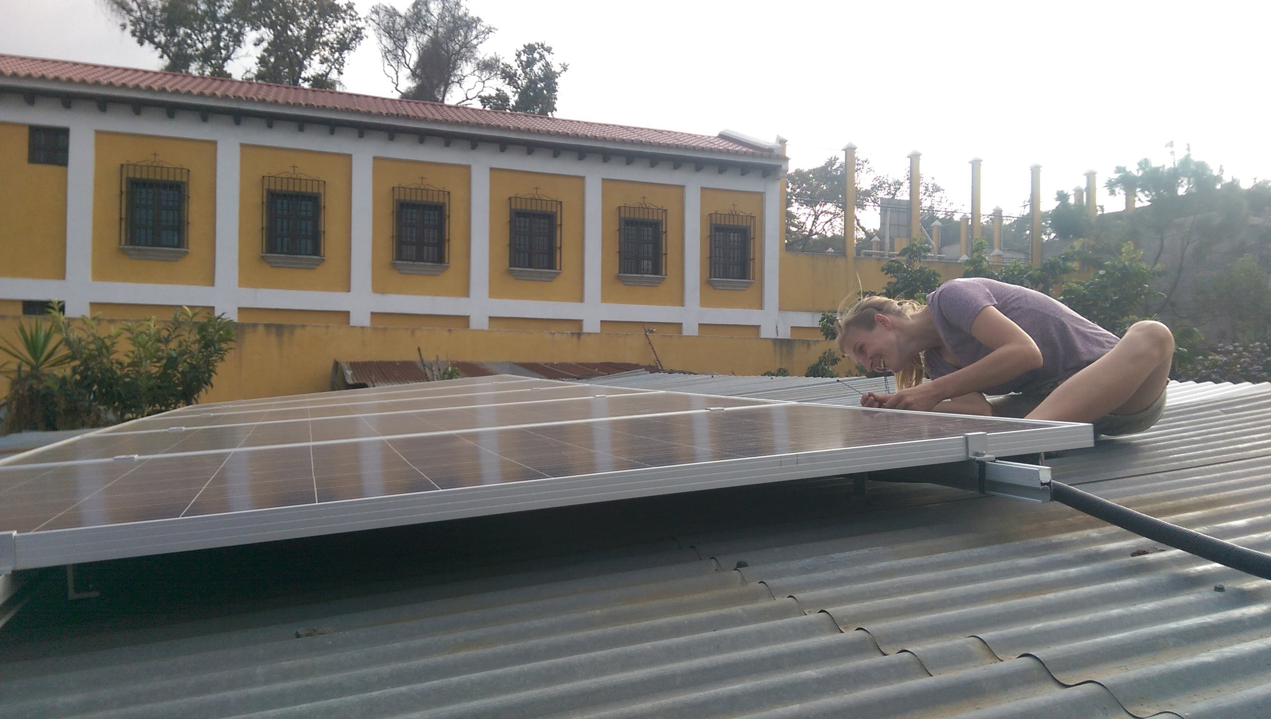 Linda from Lux Aeterna installing three new solar panels on the roof of the dry mill.