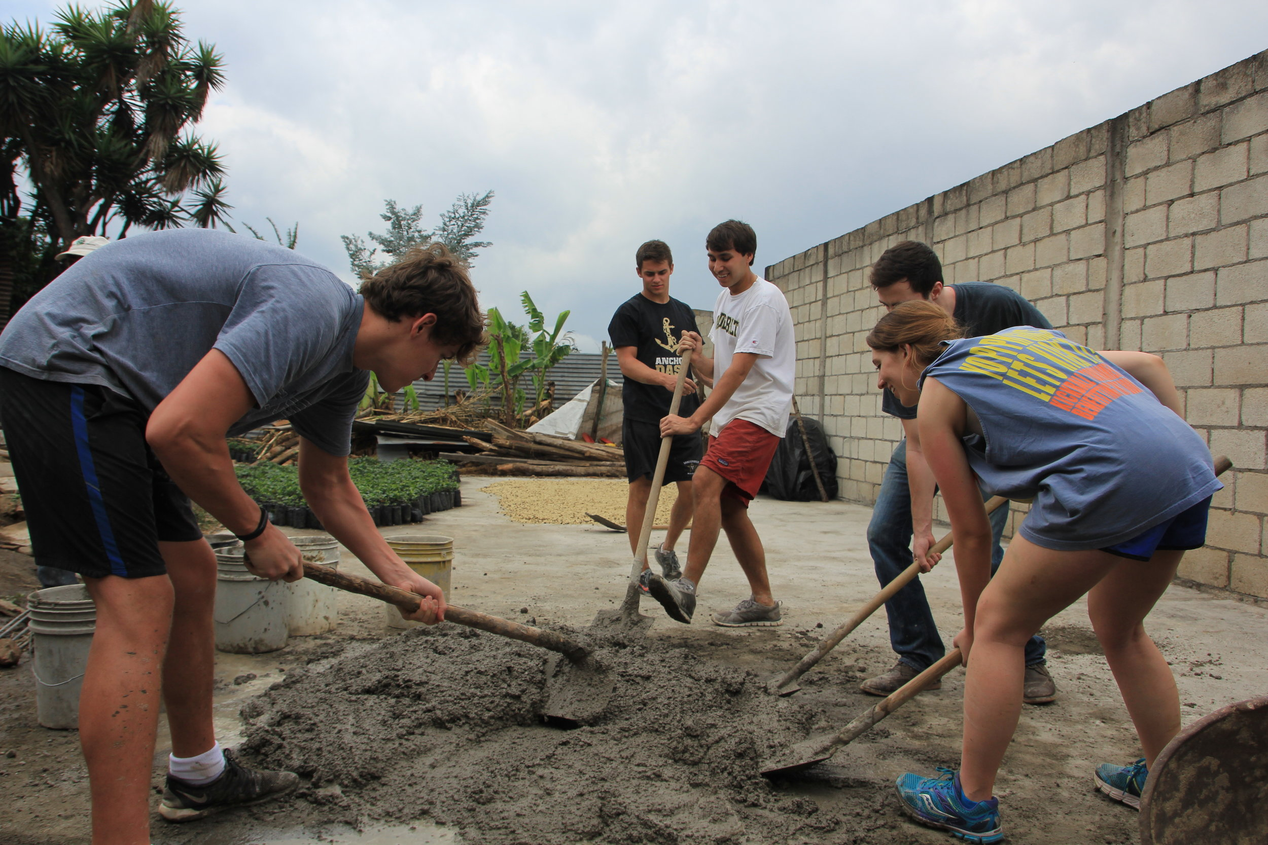 Student's mixing cement to build a wall with Juan Carlos to protect his drying patios.