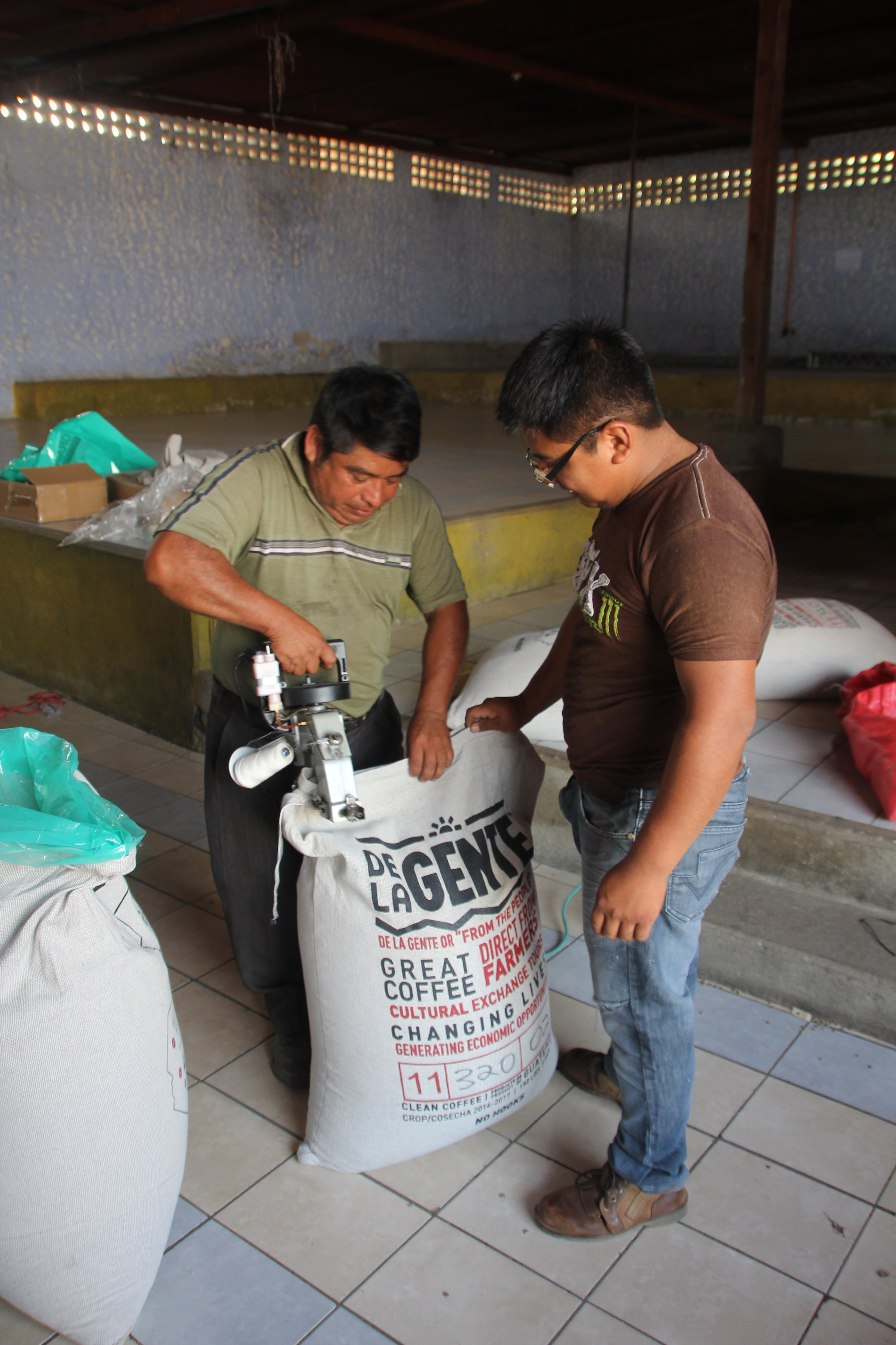 Fredy and his son sewing the bags shut, the final step in the bagging process