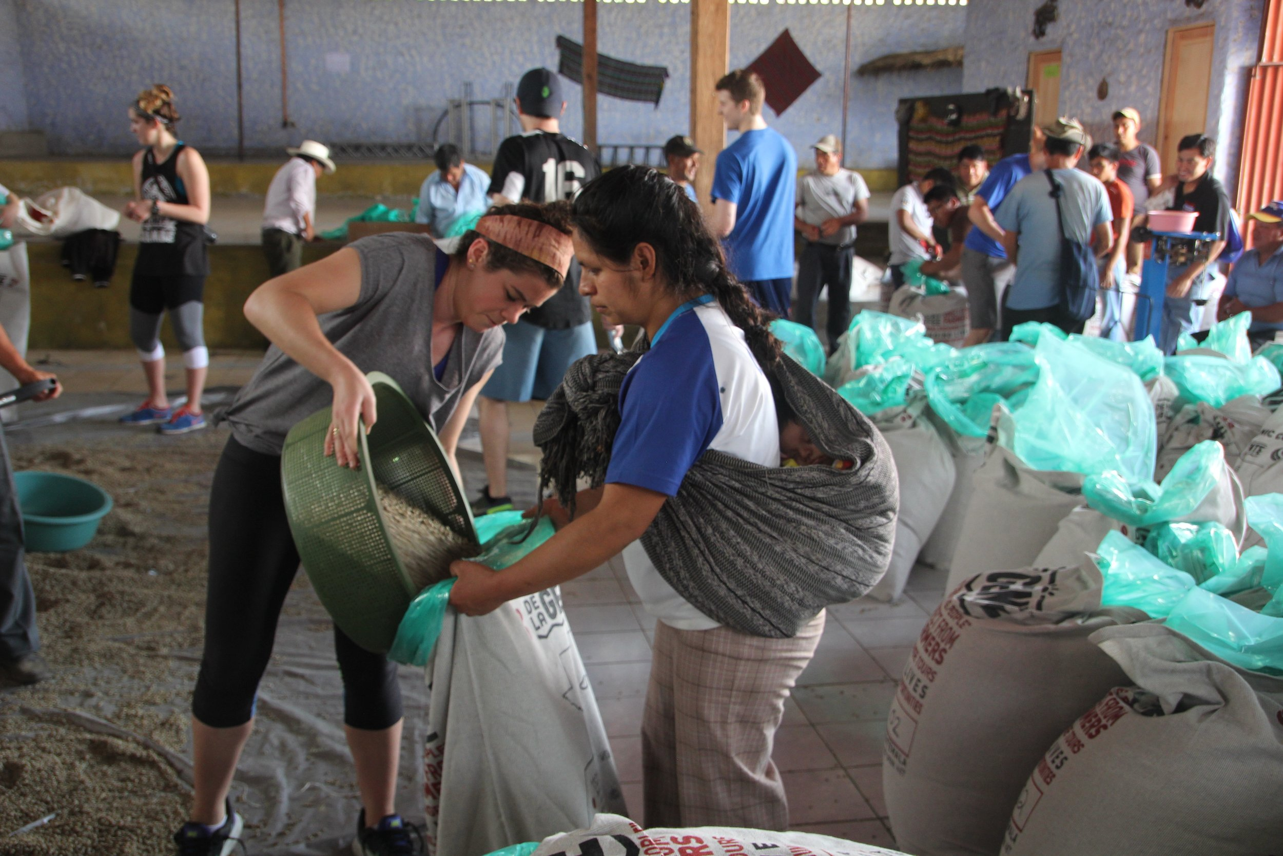 Lesbia and a volunteer bagging the coffee for export into the new upcycled textile sacks