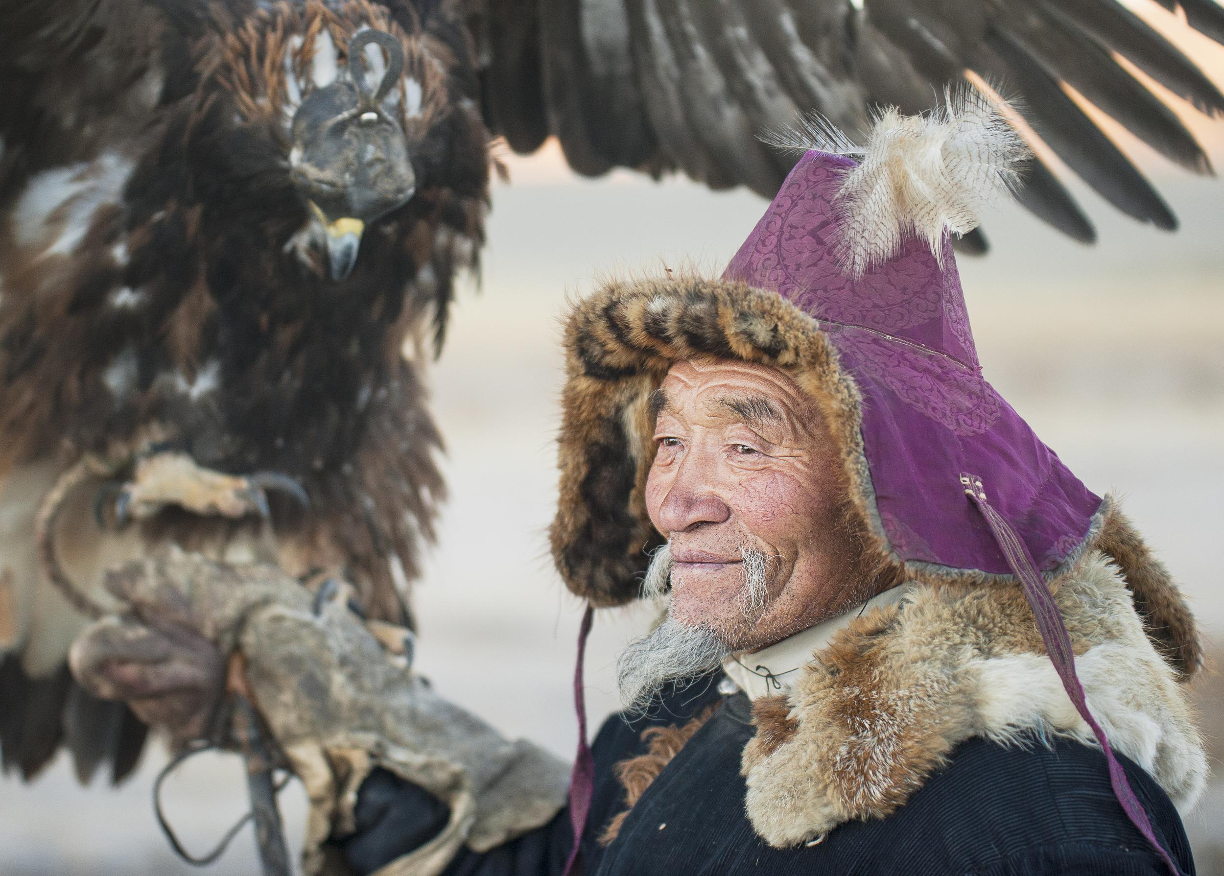 elderly kazakh eagle hunter posign with golden eagle.jpg