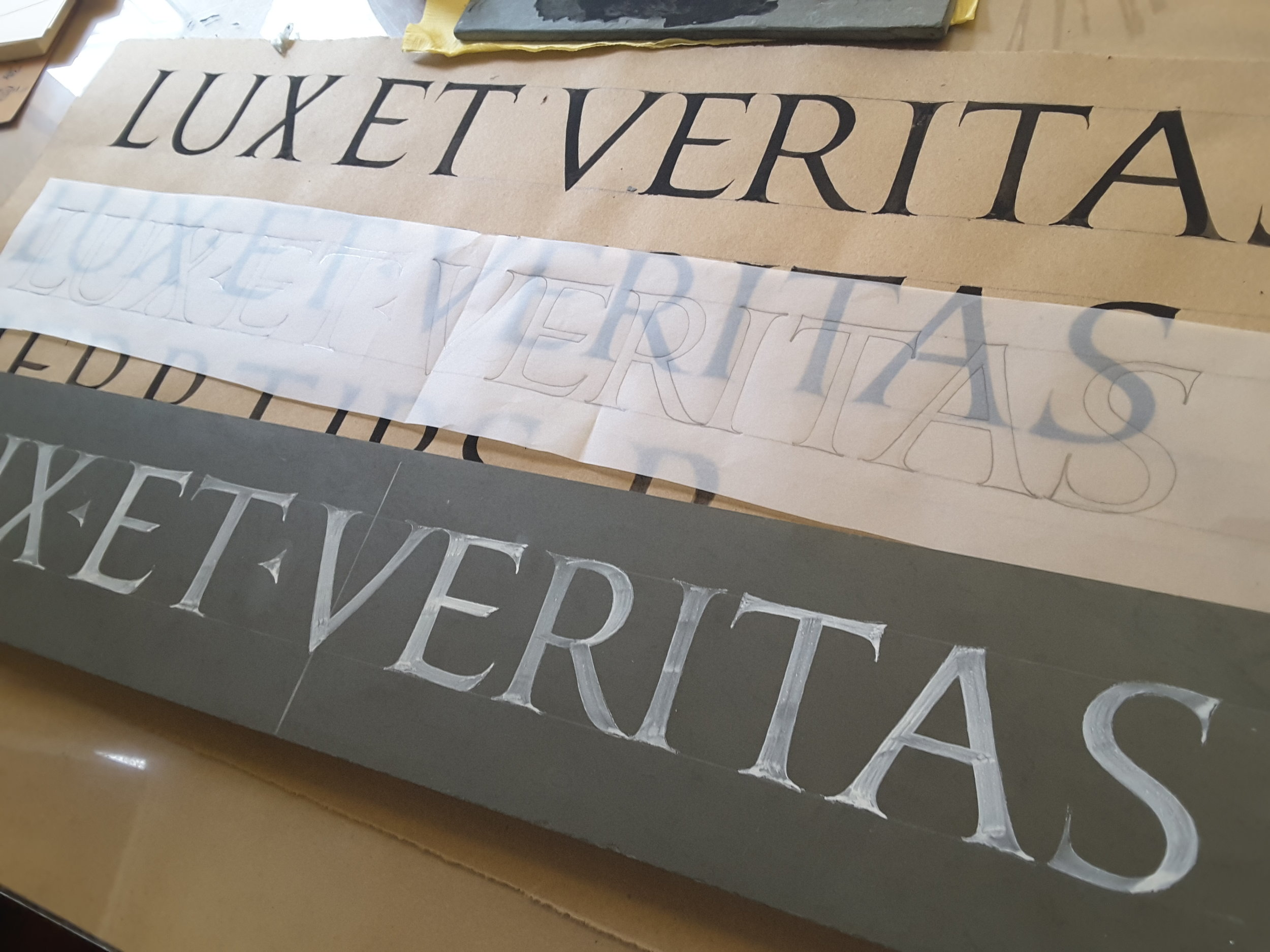 Lux Et Veritas - In 2017 I was honored to be invited to the Robert B. Haas Family Arts Library at Yale University as a Visiting Artisan. I brought along a carving demonstration and for a suitable text I reached no farther than the school's Latin motto. This picture shows the sequence relevant to all of my inscriptions: from brushwork on paper to a traced master layout to letters painted on the stone awaiting the mallet and chisel.