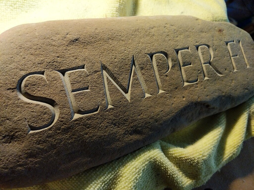 Semper Fi - A client on a limited budget approached me about carving something for a friend whose husband, a Marine pilot, had recently died. The widow is an avid gardener, so we decided that a beach stone would be the most appropriate vessel for a simple memorial, as a beach stone looks so at home in a garden.
