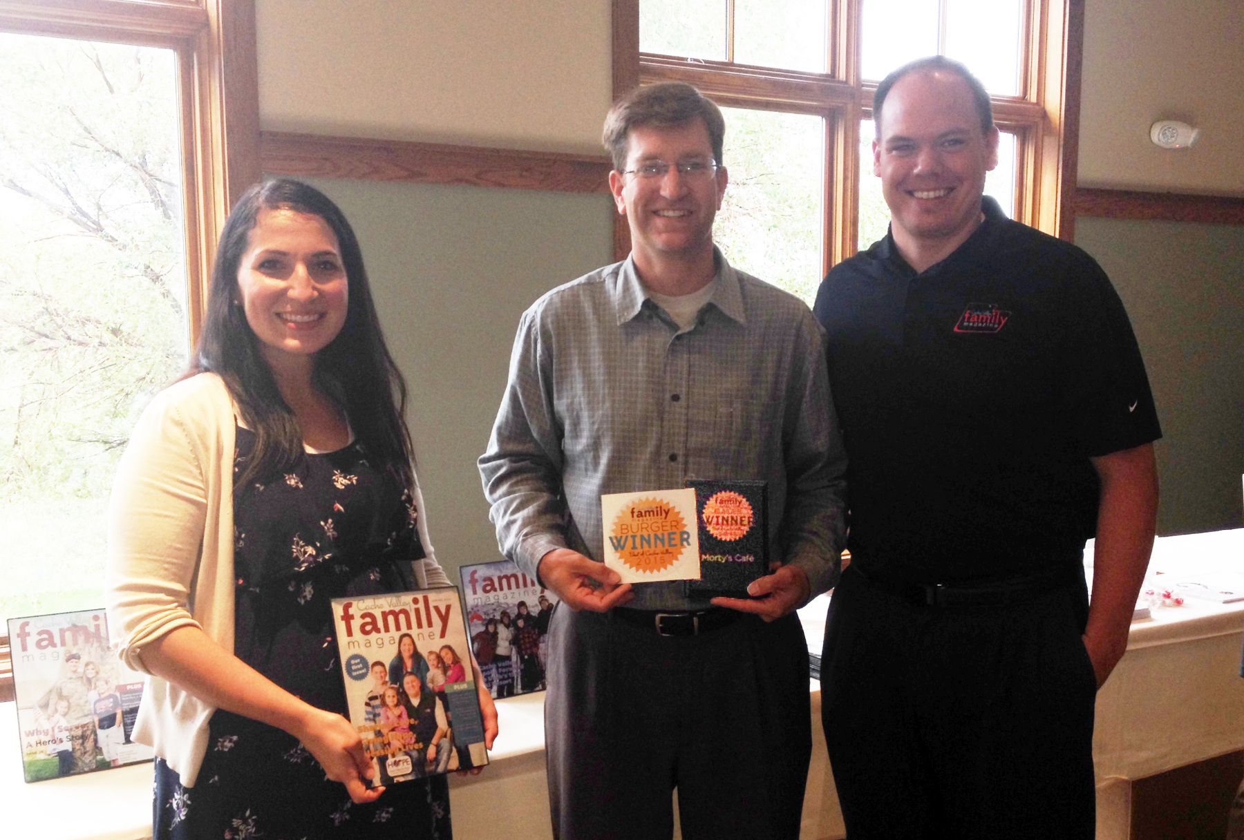 """Preston Parker, Co-Owner of Morty's Cafe, receiving the """"Best Burger"""" award from Cache Valley Family Magazine Co-Founders, Emily and Bryan Buckley."""