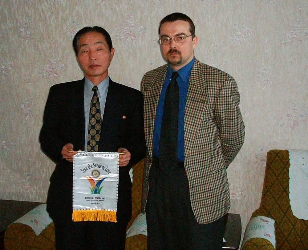 """2003 Rotary International President Bhichai Rattakul's theme slogan was """"Sow the Seeds of Love"""", which we did in Pyongyang with a Rotary Foundation Helping Grant conducted by the Rotary Club of Shanghai - with support from the Rotary Club of Taipei (Taiwan) and the Rotary Club of Makati (Philippines). Here Mr. Kim Jong Gi, Chairman of the Committee for the Promotion of International Trade receives President Bhichai's theme banner."""