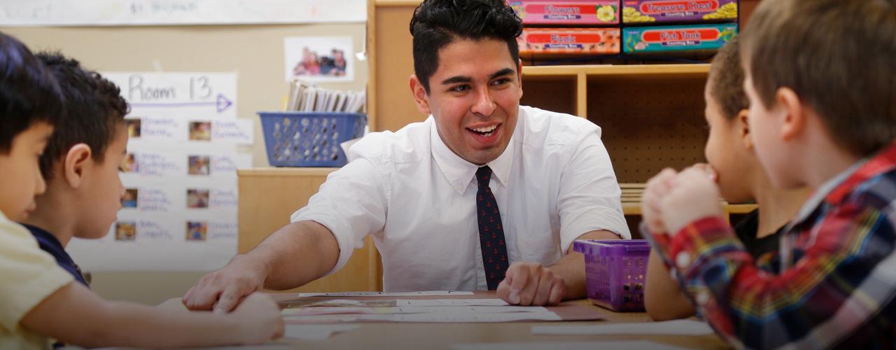 Hispanic Male Teacher Classroom.png