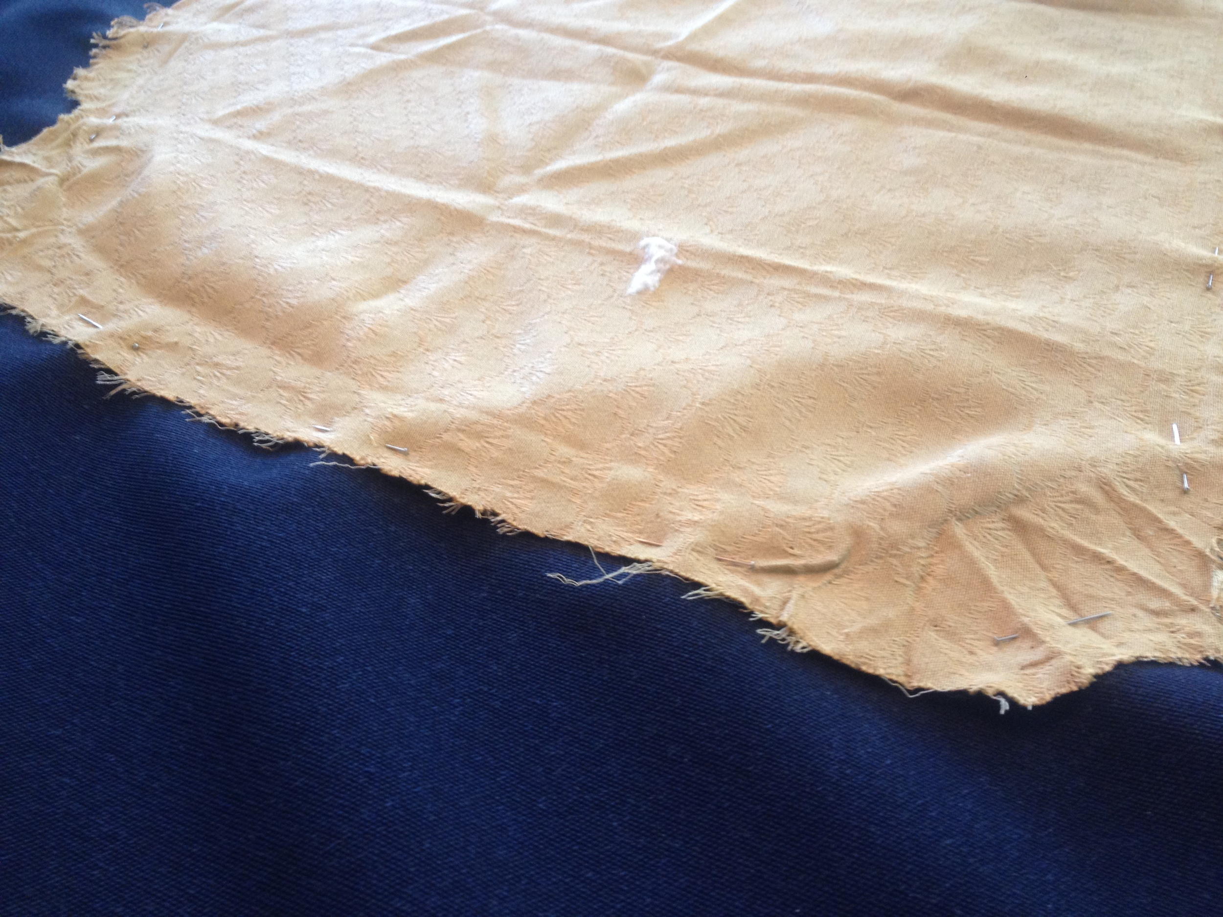 Pin down the edges of the old fabric over the new, taking into consideration the grain and pattern.