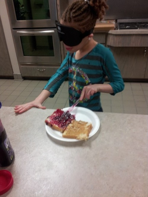 Maniya makes a PB&J under sleepshades
