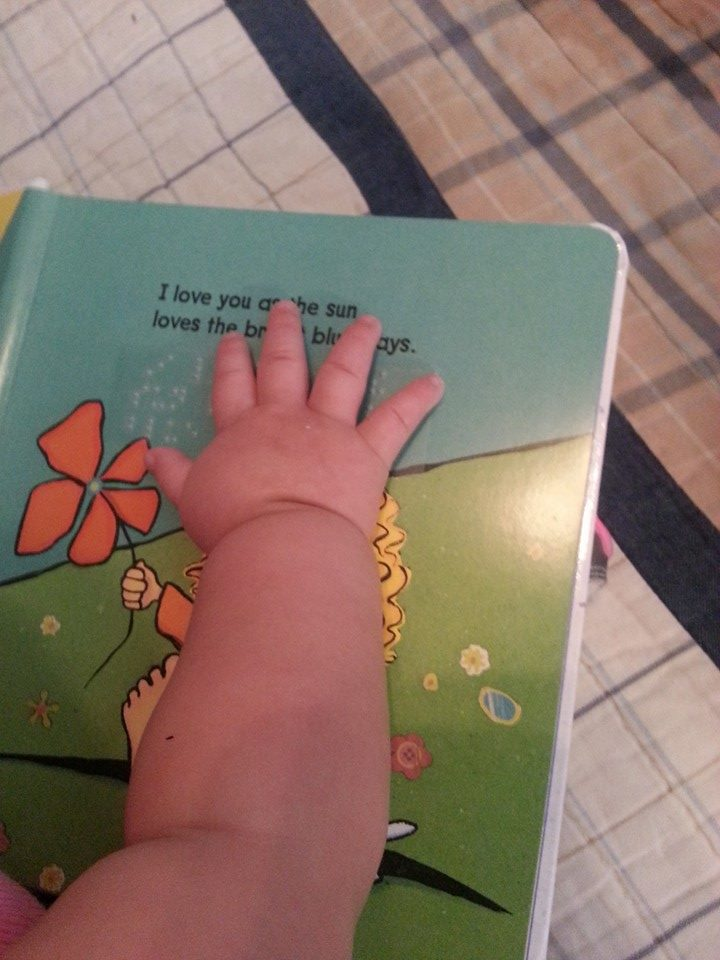 An infant's hand exploring braille on a book