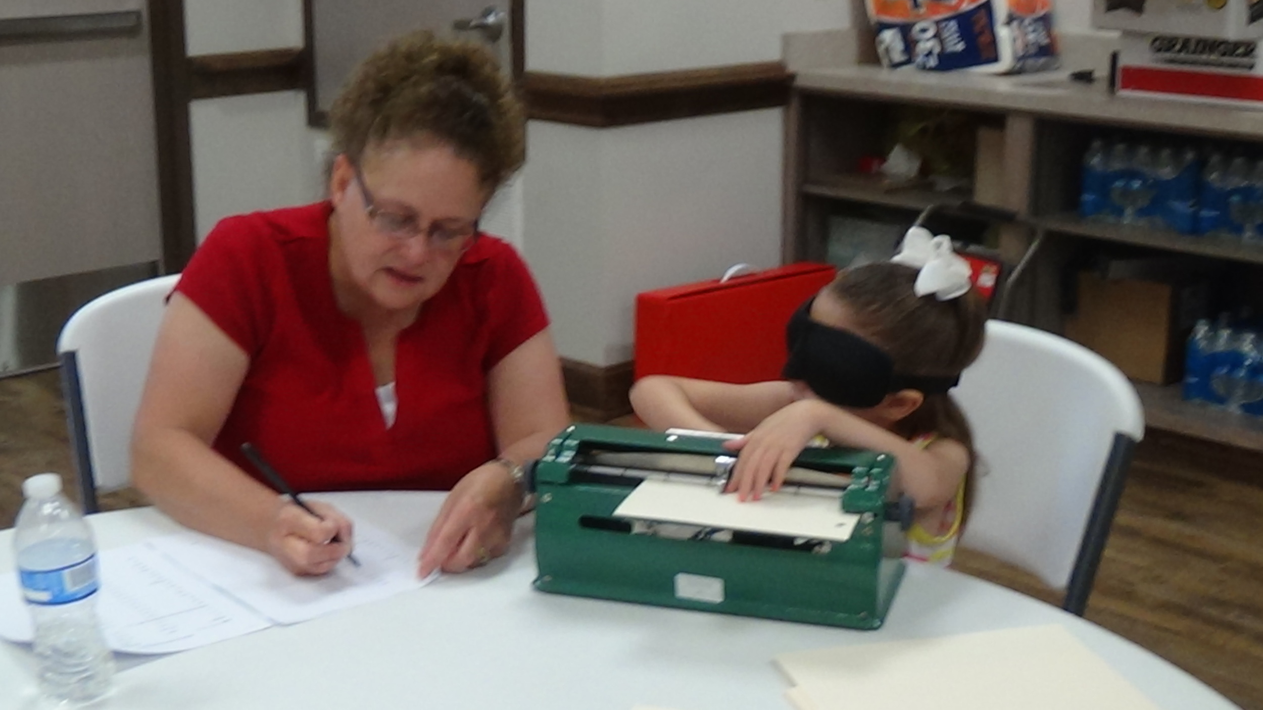 Baylee checks her braillewriting for accuracy