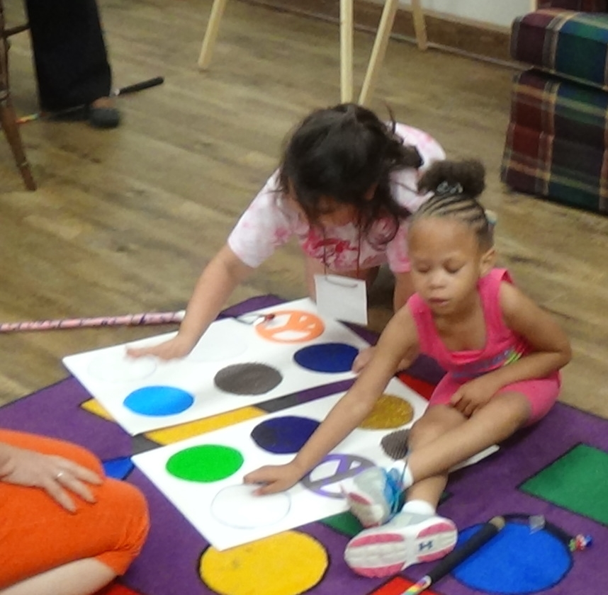 A teacher watches as two students explore a life-size, tactile, braille cell