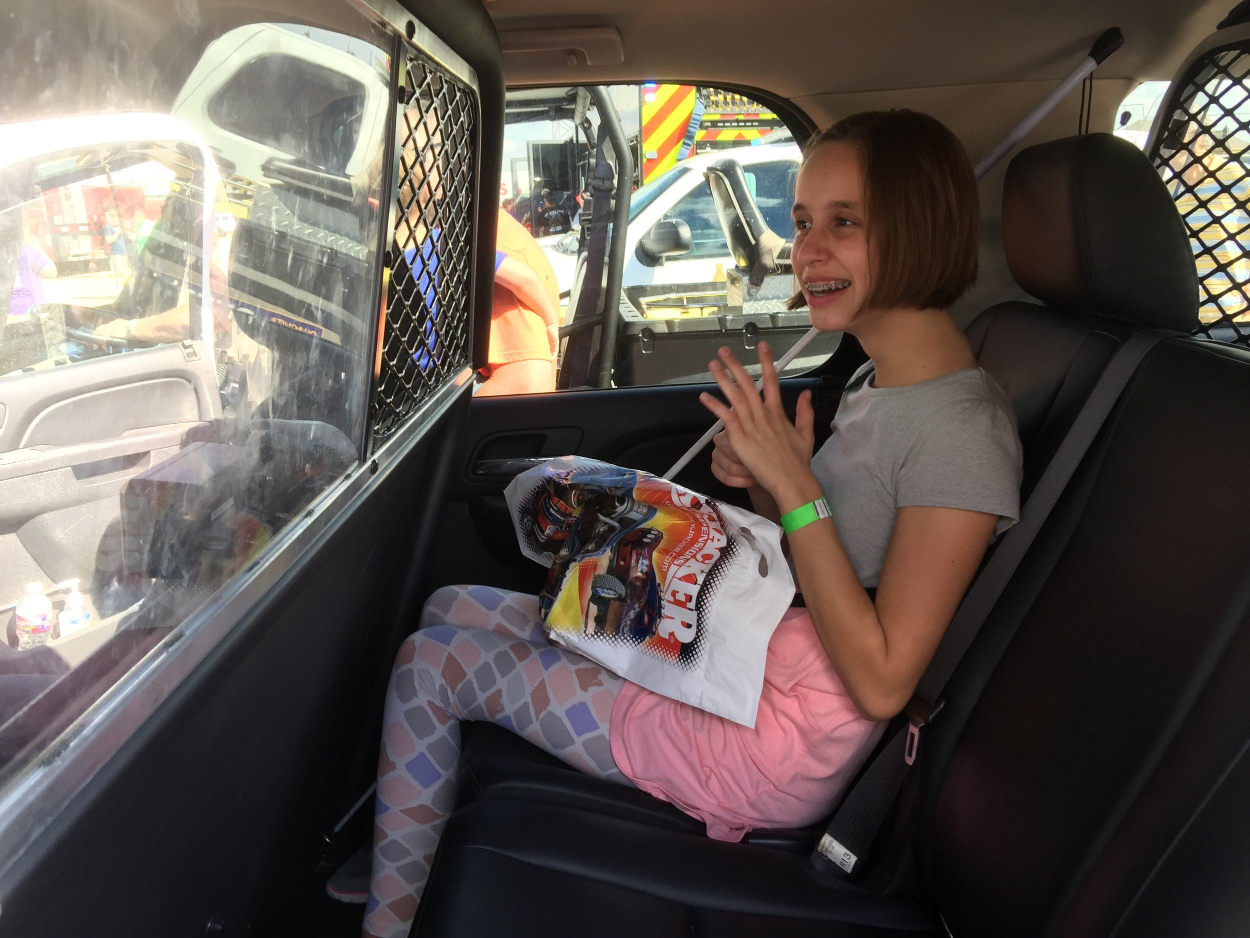 Lindsay in the back of a police car: she sure looks happy considering where she's sitting!