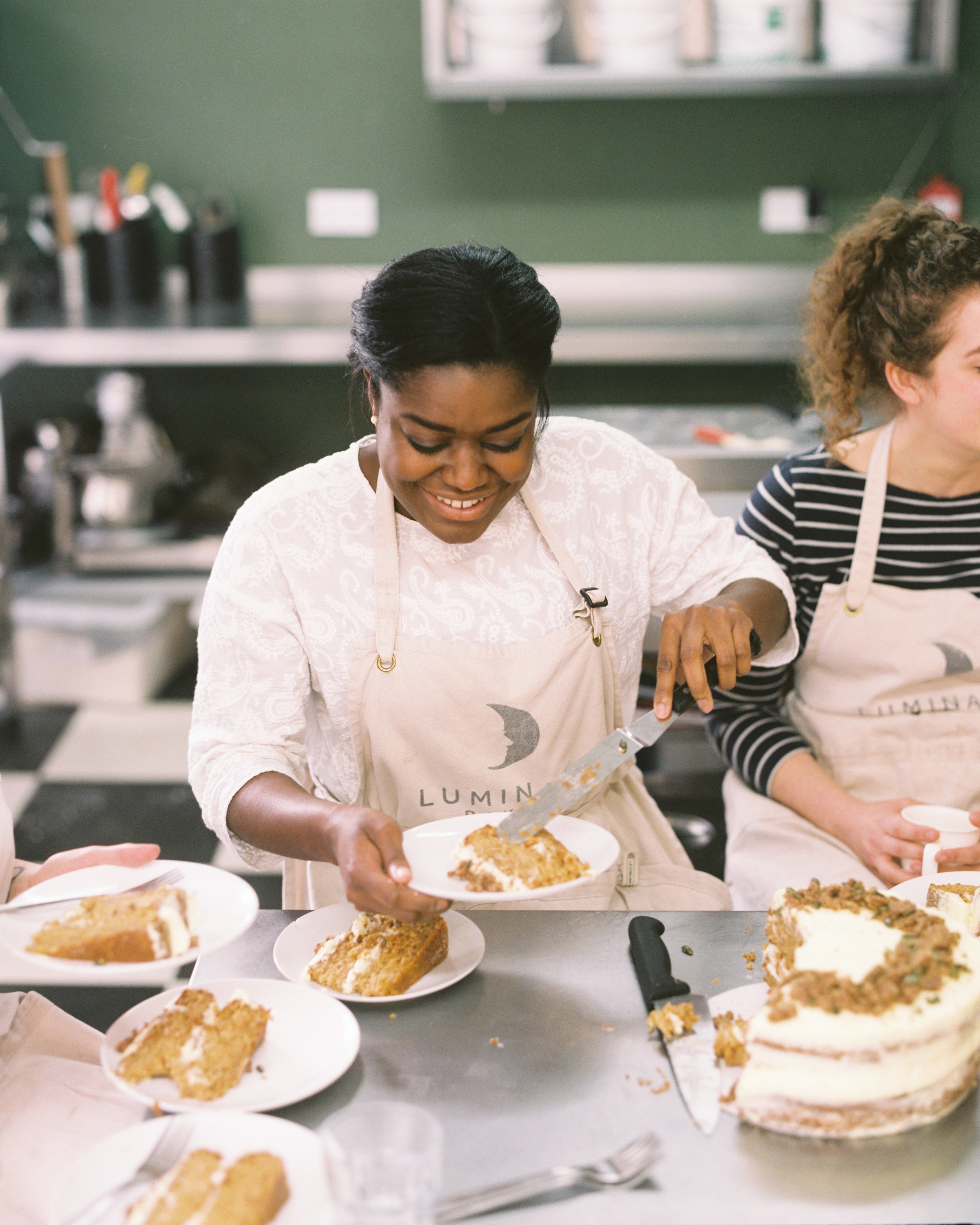 """Benjamina - 2016 Great British Bake Off quarter finalist, Benjamina Ebuehi is a Londoner who has been baking since she was 14...""""I believe that the gifts and talents we've been given should be shared and used to benefit and encourage others - I've chosen to do that through partnering with Luminary Bakery. They are doing a wonderful job of equipping, training and listening to women, and I'm so excited to be a part of the journey. ''Her website is Carrot & Crumb"""