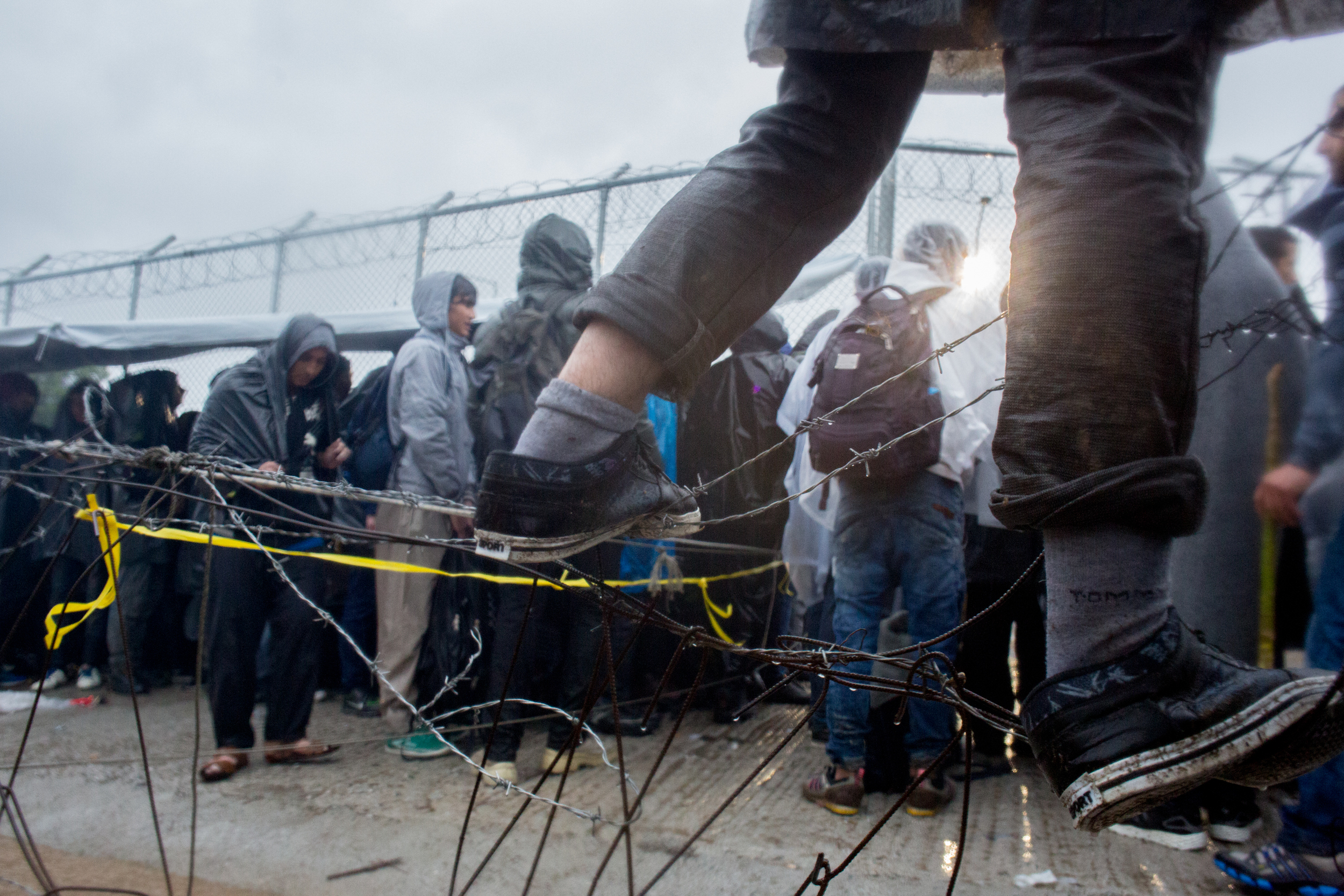 A boy stands on a fence to see over the crowds at the entrance of the Moria registration camp on Lesvos during a rainstorm. The registration process is in constant flux as Greek authorities try to deal with the large amounts of refugees arriving on the island. However, the priority is for registering families and those with proper identification papers. Single men were placed in a separate registration line. Some men said they had been waiting to be registered for three or four days.